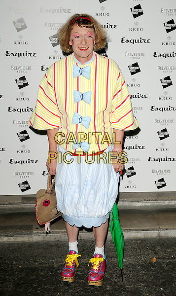 GRAYSON PERRY.The Esquire's Singular Suit Project launch party, Somerset House, The Strand, London, England..July 29th, 2009.full length blue skirt white yellow red bows stripes striped top pink ribbon brown bag purse platform shoes hearts cross-dresser .CAP/CAN.©Can Nguyen/Capital Pictures.