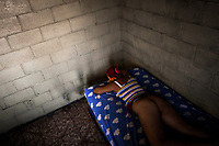 A Salvadoran sex worker lies on the bed in a room where her sexual services are offered to clients in San Salvador, El Salvador, 21 February 2014. Although prostitution is not legal in El Salvador, dozens of street sex workers, wearing provocative miniskirts, hang out in the dirty streets close to the capital's historic center. Sex workers of all ages are seen on the streets but a significant part of them are single mothers abandoned by their male partners. Due to the absence of state social programs, they often seek solutions to their economic problems in sex work. The environment of street sex business is strongly competitive and dangerous, closely tied to the criminal networks (street gangs) that demand extortion payments. Therefore, sex workers employ any tool at their disposal to struggle hard, either with their fellow workers, with violent clients or with gang members who operate in the harsh world of street prostitution.