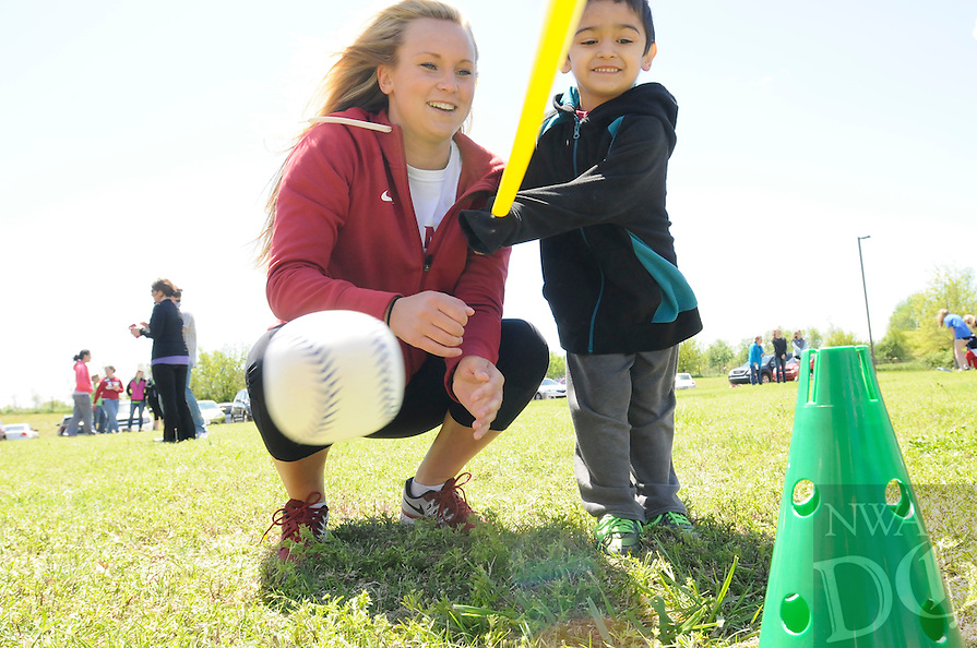 NWA Democrat-Gazette/J.T. WAMPLER --University of Arkansas soccer player Abby Sieperda, left, watches as Gabriel Limon, 4, knocks a ball off of a cone during the Kids First's first Special Olympics Young Athletes event on Monday, April 20th 2015 on the lawn west of their building in Lowell. Several University athletes and the Rogers High School cheerleaders were volunteers for the event. Around 50 special needs children between the ages of 2-5 participated in the event.