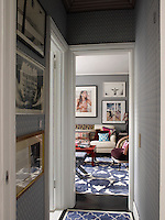 A narrow corridor lined with blue and white wallpaper connects the living room with the bedroom