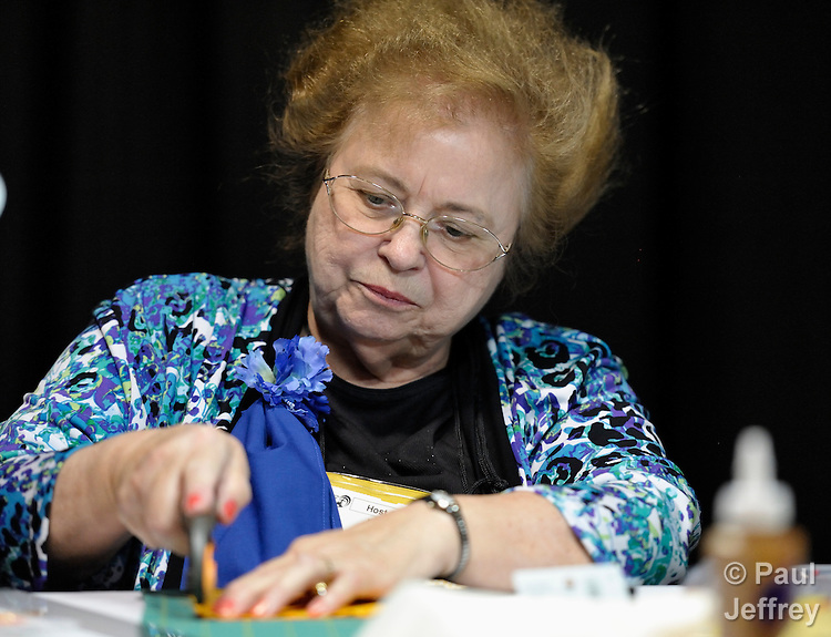 Ellen Johnsen, a member of the local host committee, works on a peace quilt in the exhibit hall of the 2012 United Methodist General Conference in Tampa, Florida.