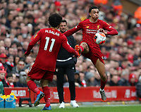 7th March 2020; Anfield, Liverpool, Merseyside, England; English Premier League Football, Liverpool versus AFC Bournemouth; Trent Alexander-Arnold of Liverpool leaps to control the ball as teammate Mohammed Salah looks on