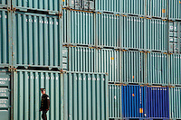 A security guard walks past stacks of containers at a holding facility on the outskirts of Shanghai, China..