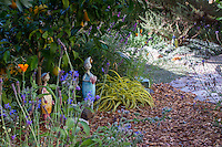 Whimsical fairies hidden under citrus tree by mulched path in Sibley drought tolerant garden, Richmond California