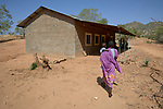 A woman carries her child into the Catholic clinic in Kauda, a village in the Nuba Mountains of Sudan. The area is controlled by the Sudan People's Liberation Movement-North, and frequently attacked by the military of Sudan. The Catholic Church has dug wells and sponsors schools and health care facilities throughout the war-torn region.