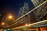 Cars and buses streak through the foreground of this lopw angle, time exposure of Hong Kong, China office building at night. The Lippo Building is at left, the Bank of China is center. NR. No restrictions.