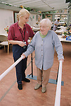 Female occupational therapist or physiotherapist assisting elderly woman to improve her balance through walking exercises.  MR