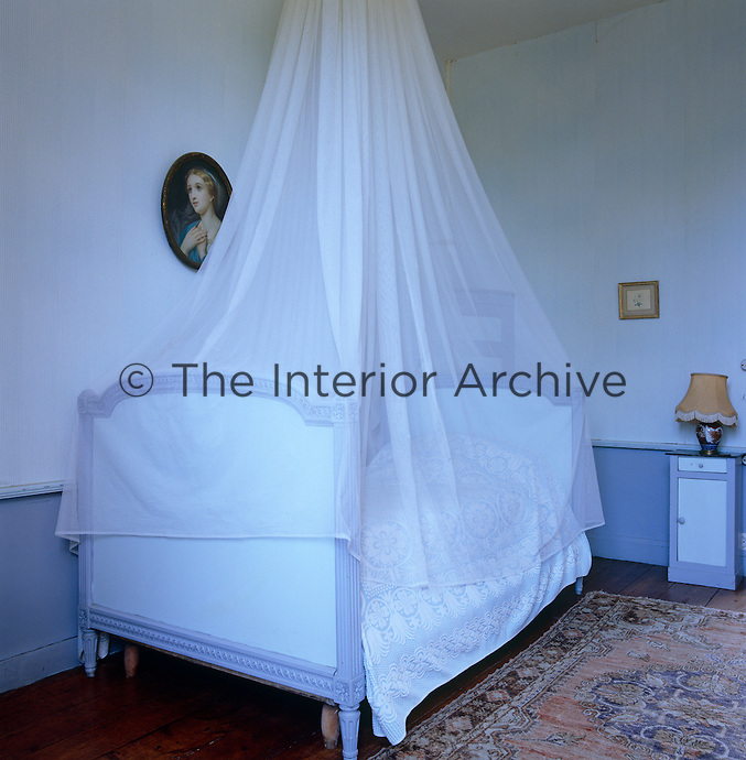 This Wedgwood blue guest bedroom is made more feminine with a collection of oval portraits and a swathe of mosquito netting over the 19th century French bed