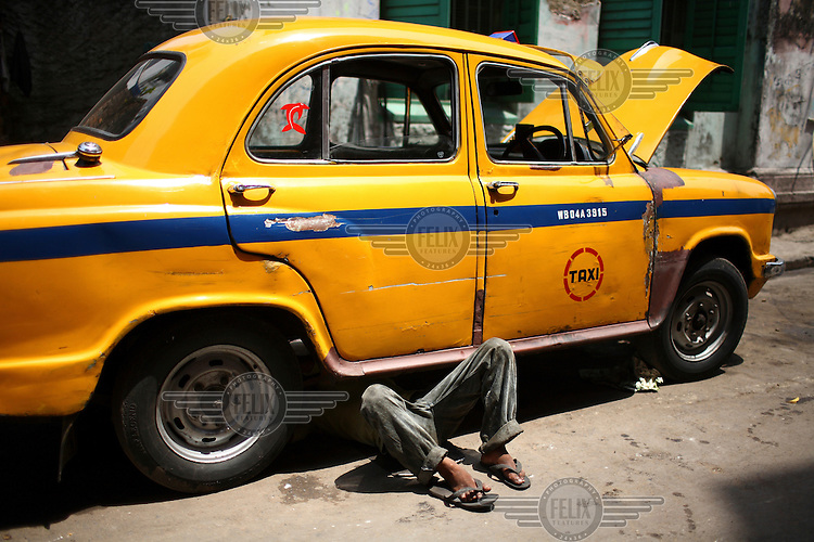 A yellow taxi cab is repaired by a mechanic in Kolkata.