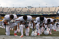 The Miami players take a Tebowing pose before the game. From left to right are Anthony Chickiillo (71), Antonio Crawford, Malcolm Lewis and Akil Craig. The Miami Hurricanes defeated the Pitt Panthers 41-31 at Heinz Field, Pittsburgh, Pennsylvania on November 29, 2013.