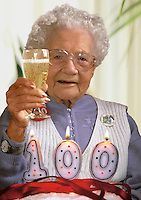 English woman on her 100th birthday toasting her family with a glass of champagne.  Birthday cake and candles on the table in front of her..
