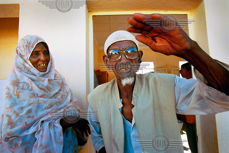 An old man wears a pair of glasses donated by the  Scandinavian NGO Vision for All. The charity collects old glasses for use in the developing world. Teams of student opticians visit rural villages setting up eye clinics, prescribing and handing out the appropriate glasses.