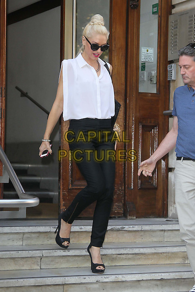Gwen Stefani in Central London, England..3rd October 2011.full length black trousers white sleeveless shirt blouse sunglasses shades hair up bun open toe shoes stairs steps braid plait.CAP/HIL.©John Hillcoat/Capital Pictures .