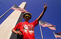Boy in red T-shirt below Washington Monument with flags in Washington DC, USA