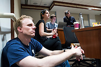 """Sam Carson, 28, (from front left), Monica Giannone, 29, Brandon Kappy, 26, and Jesse Erin Posner, 27, listen from the back of the room as New York Assemblyman (79th District) and Vice Chair of the Democratic National Committee Michael Blake speaks to a live audience during a session of Resistance School in the Starr Auditorium in the Belfer Building of Harvard University's John F. Kennedy School of Government, on Thurs., April 27, 2017. The four are involved in the production of Resistance School: Carson led the logistics group volunteers before the lecture; Giannone is one of the organization's co-founders and is in charge of logistics, content, and tech, during the livestreams; Kappy is the group's Digital Director; and Posner is a production designer. Carson and Giannone are Master in Public Policy grad students at the Kennedy School. Kappy is an MD and MPP student. Posner works in Harvard's Department of Visual and Environmental Studies.  Blake's lecture was titled """"How to sustain the resistance long term.""""  The lecture, which was the fourth such session and the final in what the group calls the """"first semester"""" of Resistance School, was also streamed live on the internet. Resistance School was started by progressive graduate students at Harvard after the Nov. 8, 2016, election of President Donald Trump. Resistance School describes itself as a """"practical training program that will sharpen the tools [needed] to fight back at the federal, state, and local levels."""" The live lectures are streamed and archived online alongside other information on the Resistance School website. During the lectures, teams of volunteers engage with followers on social media, including Facebook and twitter, sharing soundbytes, quotations, and supplementary materials as the lectures happen."""