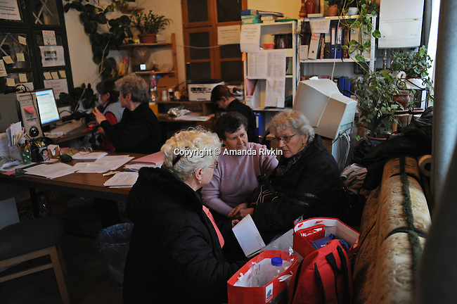"""Iren Istvanne Nemeth, 71, is comforted by church volunteers, a few days after being released from the hospital from burns caused by an industrial accident resulting from a rupture in a toxic alumina sludge reservoir at a nearby plant and the same day she began to move into the homeless shelter established by the church, """"New Beginnings,"""" in Devecser, Hungary on November 22, 2010.  Istvanne Nemeth lost her son, Istvan, 52, in the accident and was left homeless in the wake of an industrial accident at the MAL plant in nearby Ajka, Hungary on October 4, 2010, and has been staying with her daughter, Erzsebet, since then but says her daughter's extreme medical difficulties mean the solution must be a temporary one; """"I have had a difficult life,"""" Istvanne Nemeth said, expressing outrage at watching the director of the MAL plant responsible for her injuries and current state deny the hazard caused by the accident on television while she was in the hospital for six weeks in Budapest."""