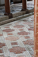 The striking chain motif pattern of the floor is constructed using quarried red stone combined with local white stone, indented to stop the horses slipping