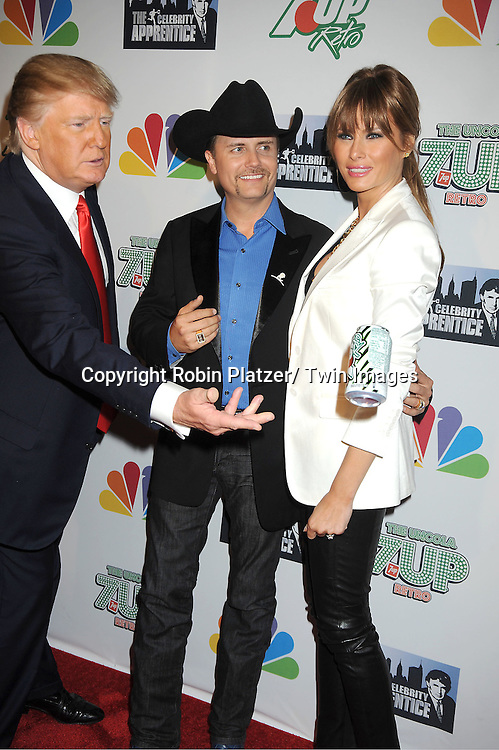 "Donald Trump, John Rich and Melania Trump posing for photographers at ""The Celebrity Apprentice"".Season Four Finale Party on May 22, 2011 at The Trump Soho Hotel in New York City."