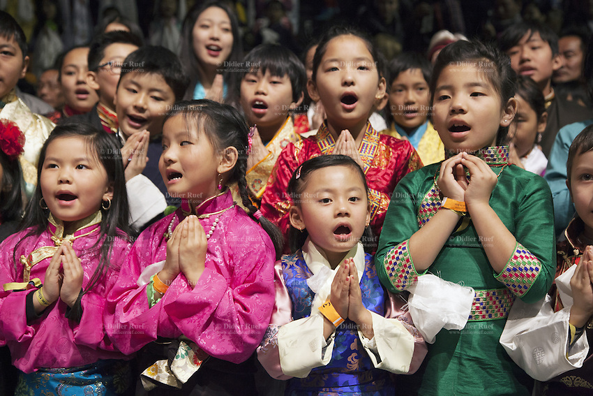 "Switzerland. Basel. St. Jakobshalle. A group of tibetan, men and women, dressed in traditional clothing sing for His Holiness the Dalai Lama. They hold their hands kept close to the chest in devotional attitude with the palms and fingers joined as a sign of respect. The gesture is also called the simple namaste (prayer) position (means ""I bow to you.""). 8.02.2015 © 2015 Didier Ruef"