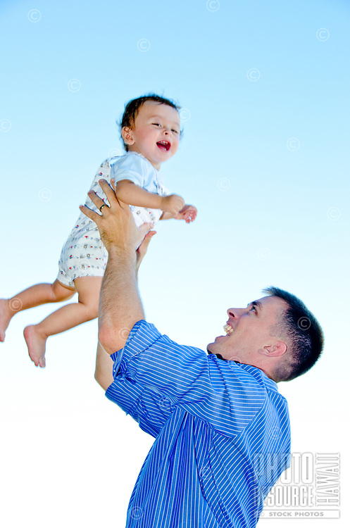 Military dad holding baby boy up against a blue sky on a sunny day in Hawaii