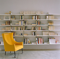 A yellow armchair by Vico Magistretti and Birgit Lohmann stands in front of aluminium sectional wall-mounted book shelves