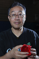 New York, NY, USA - June 24, 2011: Toshikazu Kawasaki, original Origami designer and folder from Japan at the OrigamiUSA Convention in New York City holding his creation, a Kawasaki Rose.