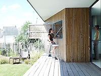 The bar between the kitchen and covered terrace is situated in a booth covered in sequoia-wood laths with a large hatch