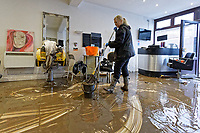Pictured: Louise Bedgood clears up mud from the floor of Lougos hair dressers. Monday 17 February 2020<br /> Re: Cleanup after storm Dennis in Oxford Street, Nantgarw, Wales, UK.