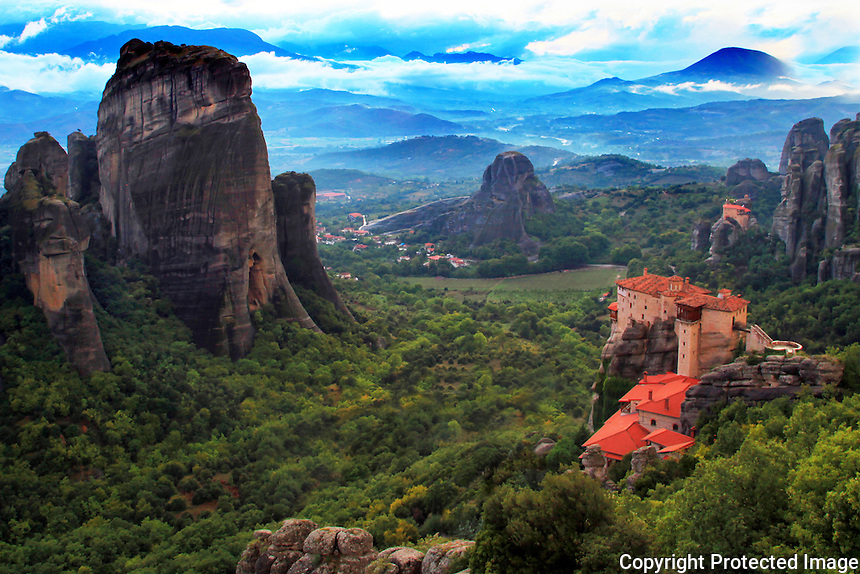"""The Metéora (Greek: Μετέωρα, pronounced [mɛˈtɛoɾɐ], literally """"middle of the sky"""", """"suspended in the air"""" or """"in the heavens above"""" — etymologically related to meteorology) is one of the largest and most important complexes of Greek Orthodox monasteries in Greece. There are six monasteries that are built on natural sandstone rock pillars. Pictured in the foreground is The Holy Monastery of Rousanou taken in the evening just after a rain storm.  The nearest town is Kalambaka. The Metéora is included on the UNESCO World Heritage List."""