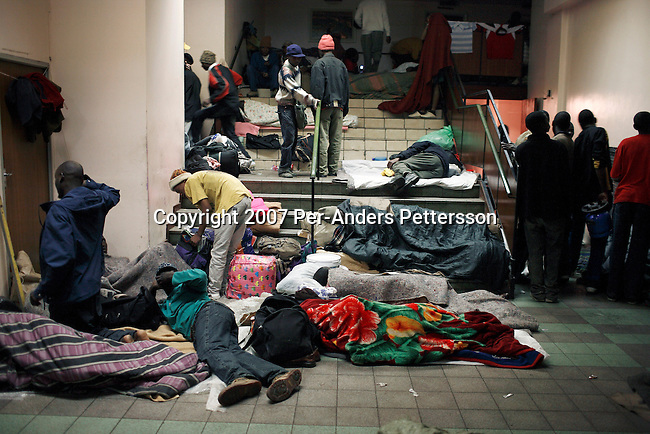 JOHANNESBURG, SOUTH AFRICA JULY 24: Unidentified refugees from Zimbabwe prepare to sleep in the Central Methodist Church on July 24, 2007 in central Johannesburg, South Africa. Thousands of refugees sleep here in a four-story building in bad conditions. Millions of Zimbabweans has fled the country since 2000, to look for a better life in South Africa. .(Photo by Per-Anders Pettersson/Getty Images).