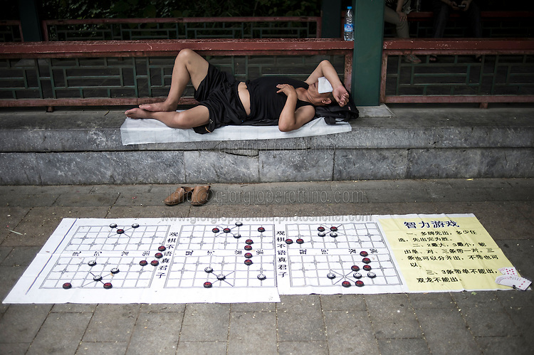 """A Chinese man takes a rest on the streets close to his Mahjong Chinese Chess display in Beijing, China, July 21, 2014. <br /> <br /> This image is part of the series """"24/7"""", an ironic view on restless and fast-growing Chinese economy described through street vendors and workers sleeping during their commercial daily activity. <br /> <br /> © Giorgio Perottino"""