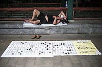"A Chinese man takes a rest on the streets close to his Mahjong Chinese Chess display in Beijing, China, July 21, 2014. <br /> <br /> This image is part of the series ""24/7"", an ironic view on restless and fast-growing Chinese economy described through street vendors and workers sleeping during their commercial daily activity. <br /> <br /> © Giorgio Perottino"