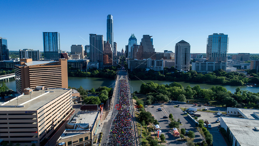 Aerial view from a drone of Runners on the Congress Avenue Bridge during the Statesman Cap10K in downtown Austin, Texas during a beautiful morning sunrise.