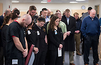 NWA Democrat-Gazette/BEN GOFF @NWABENGOFF<br /> Staff and guests bow their heads in prayer Wednesday, Feb. 21, 2018, during a ribbon cutting and blessing at Mercy Therapy Services on Horsebarn Road in Rogers. Mercy celebrated the renovation of the facility, quadrupling the space to 10,000 square feet, with more open exercise space, new equipment and curtained-off individual treatment rooms.