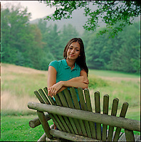 Woman, leaning over bench, looking at camera