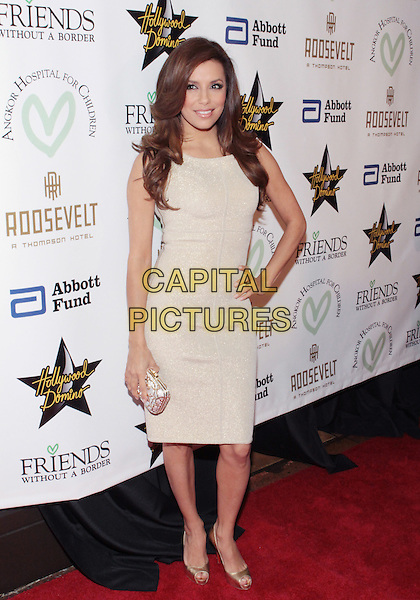 EVA LONGORIA PARKER .Attending the first annual LA Friend Without A Border & Angkor Hospital For Children Gala Benefit held at The  Roosevelt Hilton Hotel, Hollywood, California, USA, .10th December 2009..full length beige dress gold shoes sleeveless hand on hip peep toe clutch bag .CAP/ADM/TC.©T.Conrad/Admedia/Capital Pictures