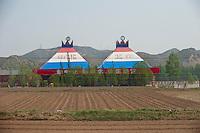 Daytime landscape view from a train of a commercial building near Dàtóng Shì Chéng Qū in Shānxī Province, China  © LAN