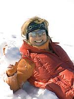 Deutschland, Frau mit Schneeball sitzt im Schnee | Germany, woman with snowball sitting in the snow