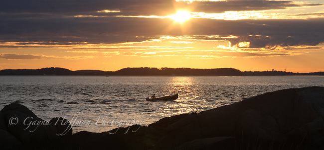 Small motor boat running along the coast of Annisquam at sunset.