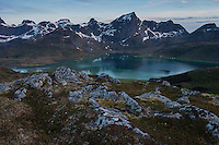 Mountains rise over calm water of Flakstadpollen, Flakstadøy, Lofoten Islands, Norway