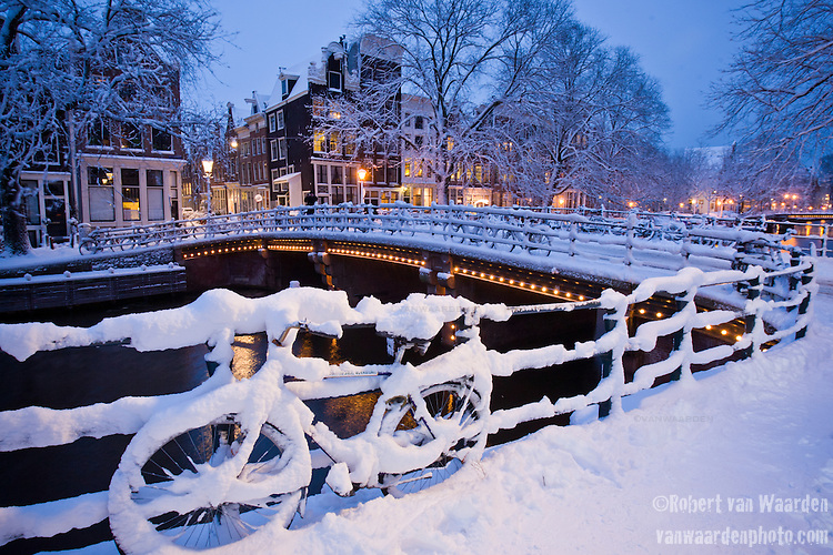 Snow covered bike and the canals of amsterdam