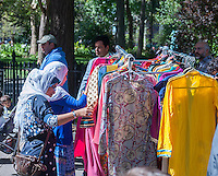 Muslim women wearing clothing proscribed by their religion shop at a street fair after the American Muslim Parade in New York on Sunday, September 14, 2014. (© Richard B. Levine)