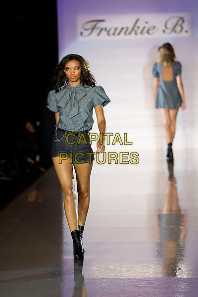 MODEL.Mercedes-Benz Spring 2007 L.A. Fashion Week - Frankie B Spring 2007 Runway Show held at Smashbox Studios, Culver City, California, USA, 16 October 2006..full length fashion catwalk modelling black ankle boots flower in hair clip grey shorts denim blouse pussybow shirt top.Ref: ADM/ZL.www.capitalpictures.com.sales@capitalpictures.com.©Zach Lipp/AdMedia/Capital Pictures.