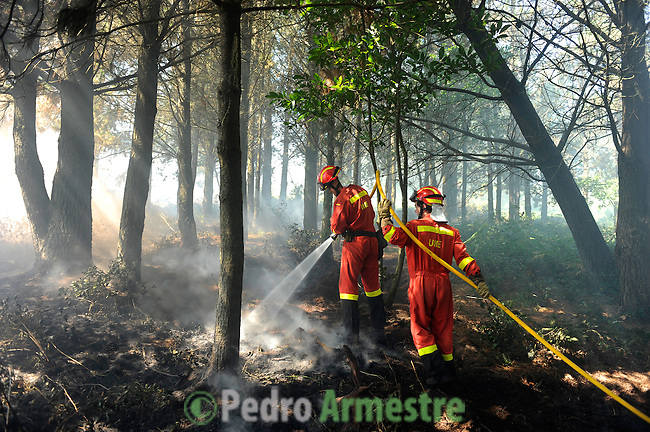 Members of the Spanish Army Emergency Unit (UME) works around the fire area in Boiro, on August 16, 2010, near A Coruna.  Pedro ARMESTRE