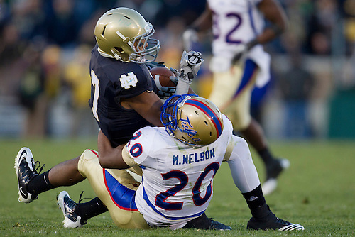 Notre Dame wide receiver TJ Jones (#7) is tackled by Tulsa defensive back Marco Nelson (#20) after catch during NCAA football game between Tulsa and Notre Dame.  The Tulsa Golden Hurricane defeated the Notre Dame Fighting Irish 28-27 in game at Notre Dame Stadium in South Bend, Indiana.