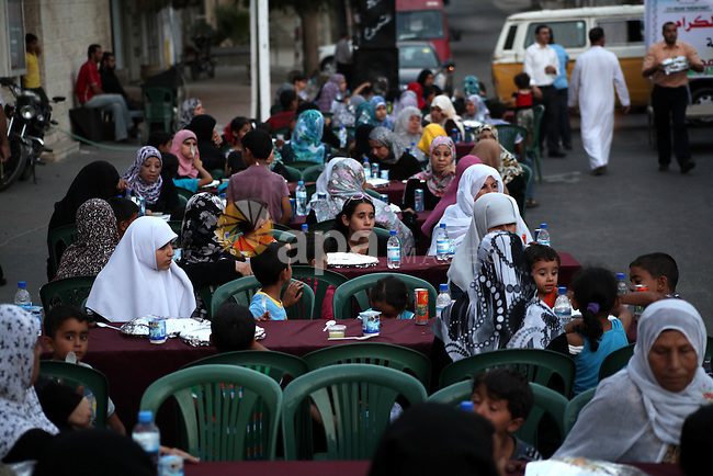"Families of Palestinian prisoners in Israeli jails attend the collective breaking fast organized by the Association of ""Wa'ed"" and funded by the Turkish relief ""IHH"" in front of the Red Cross headquarters during the holy month of Ramadan, in Gaza City on 30 July 2012. Photo by Ashraf Amra"