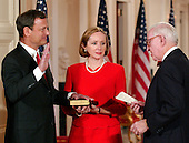 Washington, DC - September 29, 2005 -- John Glover Roberts, Jr., left, is sworn-in as the 17th Chief Justice of the United States by Associate Justice John Paul Stevens, right, in the East Room of the White House in Washington, D.C. on September 29, 2005.  His wife, Jane Sullivan Roberts, center, holds the bible..Credit: Ron Sachs / CNP