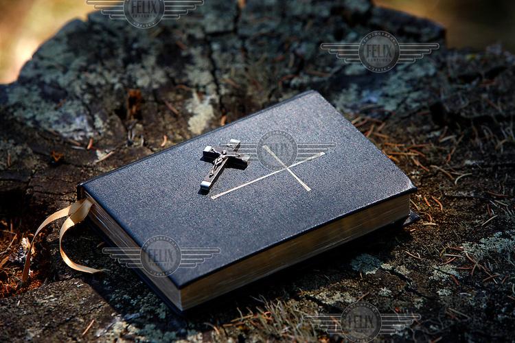A small crucifix lying on a Bible.