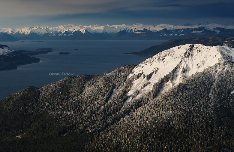 Trees are dusted with a fresh snow on mountains accenting channels of cold blue water in Southeast Alaska. South Chilkat Mountains in the background.