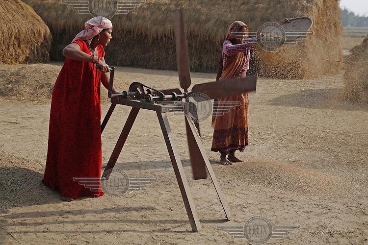 Women winnowing rice with a mechanical fan.